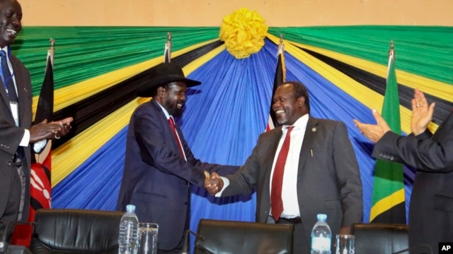 FILE - South Sudan's President Salva Kiir, left, shakes hands with rebel leader and former vice president Riek Machar, right, after signing an agreement at the end of talks in Arusha, Tanzania, Jan. 21, 2015.