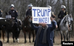 FILE - An anti-Trump protester holds a protest sign in front of mounted police outside a rally for then Republican U.S. presidential candidate Donald Trump in Cleveland, Ohio, March 12, 2016. Minorities have been especially concerned about whether Trump's xenophobic rhetoric will translate into policy.