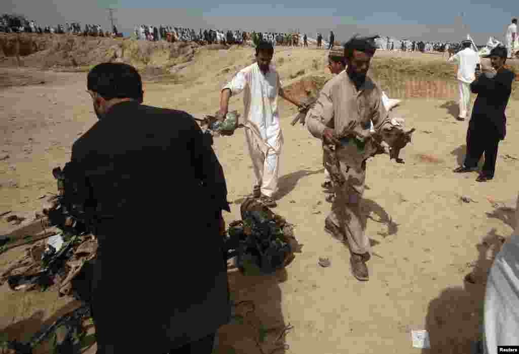 Security officials collect evidence at the site of a bomb attack in Jalozai camp in Nowshera district, northwestern Pakistan, March 21, 2013.