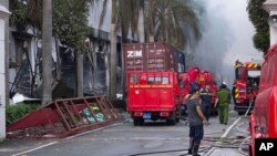 Firefighters stand across from the main entrance of Tan Than Industries as the Taiwanese bicycle factory burns, in Di An Town, Binh Duong province, Vietnam, May 14, 2014.