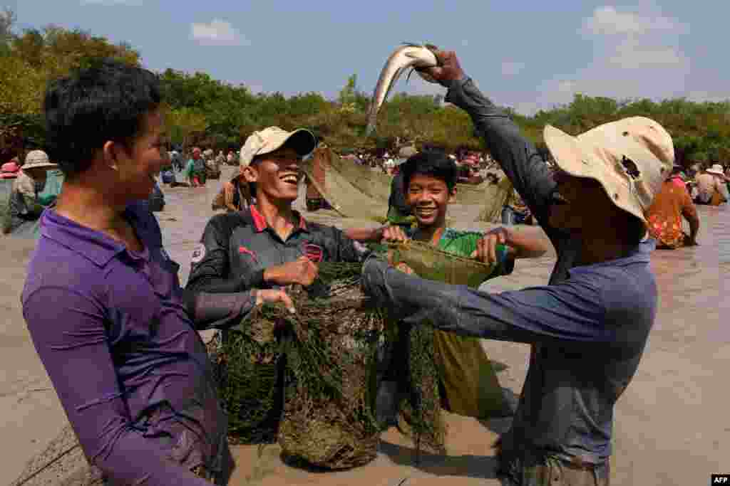 A man raises a snake fish up during the annual fish-catching ceremony at Choam Krovean commune in Tboung Khmum province, Cambodia.