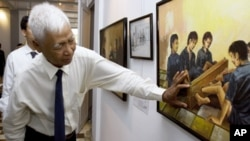 In this photo taken July 12, 2007, Khmer Rouge death camp survivor Vann Nath describes his painting during an exhibition in Phnom Penh.