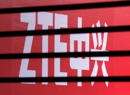 The company logo of ZTE is seen through a wooden fence on a glass door in Beijing, April 18, 2013.
