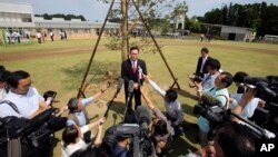 Noraha Mayor Yukiei Matsumoto, center, speaks to journalists as the town reopens four-and-a-half years after the tsunami and nuclear disaster, in Naraha, Fukushima, Japan, Sept. 5, 2015.