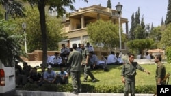 Syrian soldiers and police members secure the area near the U.S. Embassy in Damascus, July 12, 2011.