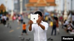 Thanh niên sử dùng máy tính bảng để chụp ảnh ở Phnom Penh