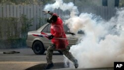 A Thai anti-government protester throws back tear gas canister at riot policemen during a clash at a sport stadium in Bangkok, Dec. 26, 2013.