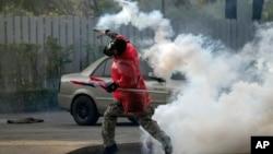 26일 태국 방콕의 반정부 시위 현장에서, 한 시위대가 경찰이 발사한 최루탄을 다시 경찰울 향해 던지고 있다.