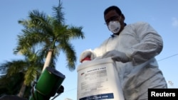 FILE - A health worker prepares insecticide before fumigating a neighborhood in San Juan, Puerto Rico, Jan. 27, 2016.