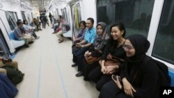 People ride on a Mass Rapid Transit (MRT) during a trial run in Jakarta, Indonesia, Feb. 21, 2019. The 10-mile system running south from Jakarta's downtown is the first phase of a development that will plant a cross-shaped network of stations across the city.
