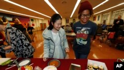FILE - Miaofan Chen, left, works her way through the dessert choices along with Thandi Glick during a potluck meal for Chinese exchange students and their host families in Denver, Jan. 27, 2017.