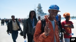 FILE - A migrant flashes the victory sign after disembarking from an Italian navy vessel at the port of Augusta, Sicily, in April. A new report highlights the potential economic benefit of migrants to host countries.