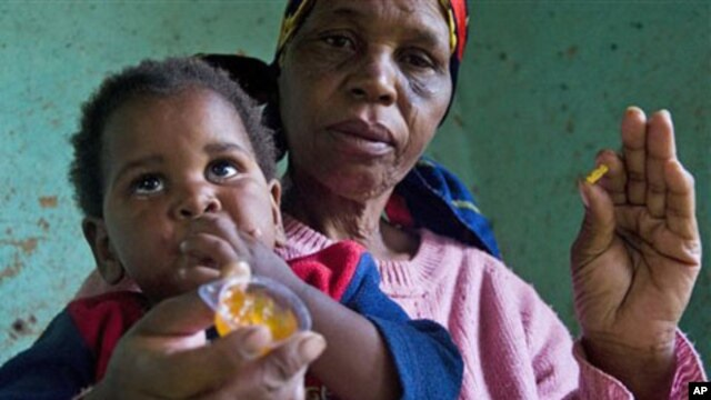 A child with HIV is given medication by a care-giver in Durban, South Africa