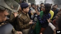 An Indian woman, right, part of a group demonstrating against the brutal gang-rape of a woman on a moving bus, argues with police officers after they were prevented from protesting in New Delhi, India, Dec. 24, 2012.