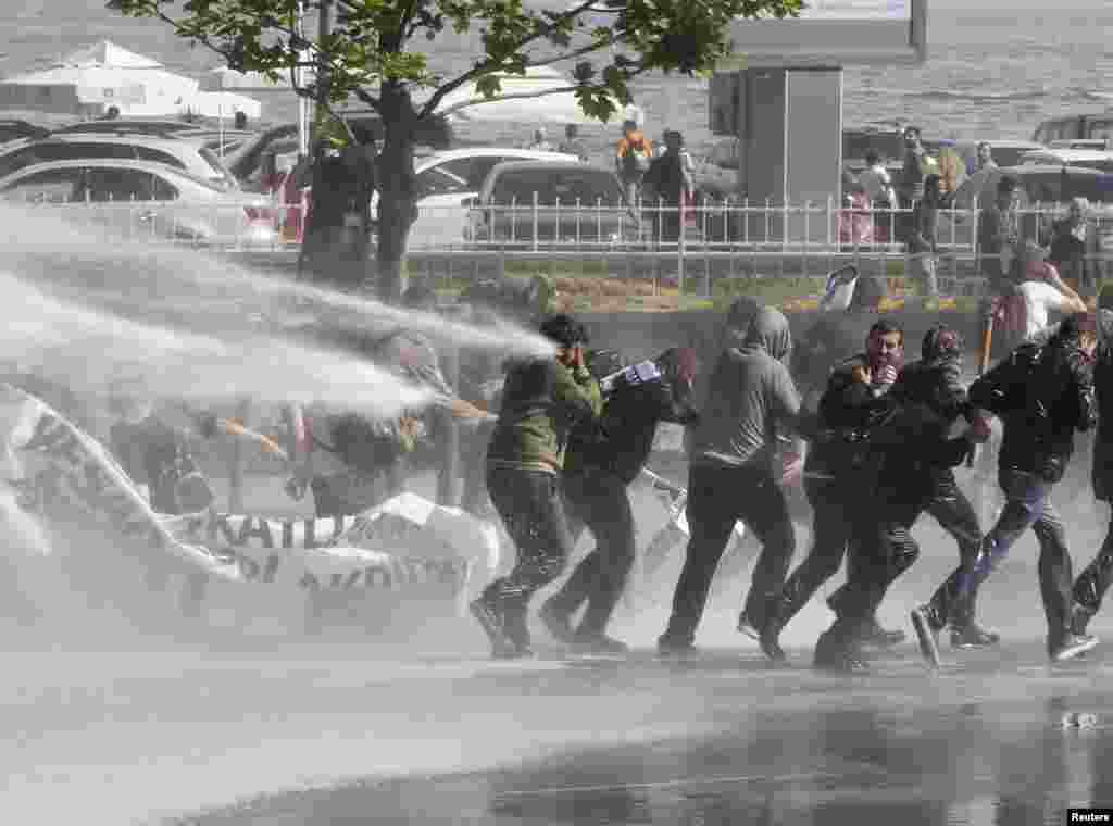Protesters clash with riot police during a protest against Turkey's Prime Minister Tayyip Erdogan and the government's foreign policy on Syria, in Istanbul, Turkey.