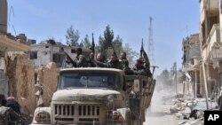 Des soldats syriens célèbrent leur victoire contre le groupe Etat islamique en Qaryatain, Syrie, le 4 Avril, ici 2016.