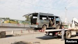 12月8日在巴格达一处爆炸地点,一名工人准备拖走被炸毁的车辆