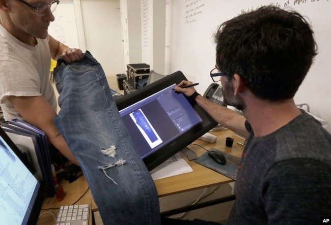 Bart Sights, head of the Eureka Lab, left, and Aykut Aygun, manager of technical innovation, give a demonstration on designing jeans at Levi's innovation lab in San Francisco, Feb. 9, 2018.