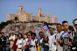 Backdropped by the Hotel Nacional, people hold Cuban flags as they wait for the motorcade transporting the remains of Cuban leader Fidel Castro in Havana, Cuba, Nov. 30, 2016.