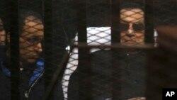 Mantan Presiden Hosni Mubarak (kanan) bersama putranya Gamal Mubarak saat hadir di pengadilan Kairo, Sabtu (29/11).