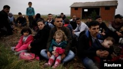 FILE - Syrian refugees who crossed the Evros river, the natural border between Greece and Turkey, rest on a field as they wait for the police to arrive and transfer them to a first reception center, near the village of Nea Vyssa, Greece, May 2, 2018.