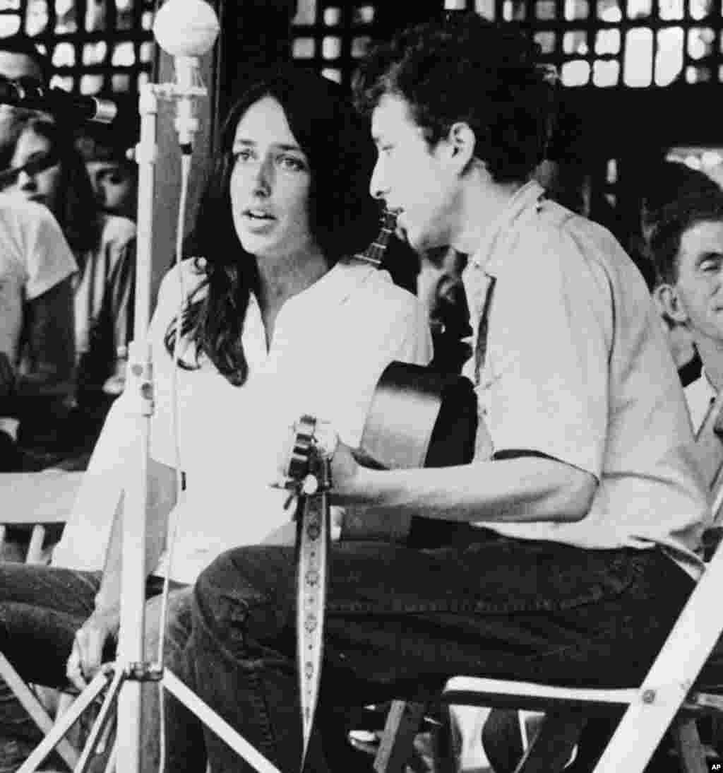1963年,卜戴倫和歌手瓊·貝茲在紐波特的爵士音樂節演唱 。