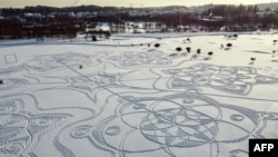 An aerial photograph shows a snow drawing made entirely of footprints on a golf course outside the Finnish capital Helsinki, in Espoo on February 10, 2021.