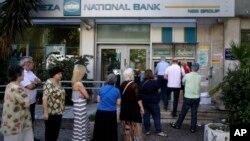 Warga Yunani antri di sebuah ATM di luar sebuah bank yang tutup di Athena, Selasa (30/6).