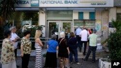 Người dân đứng xếp hàng rút tiền ở máy ATM bên ngoài ngân hàng bị đóng cửa ở Athens, Hy Lạp, hôm 30/6/2015.