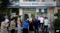 មនុស្សម្នាឈរតំរង់ជួរគ្នាដើម្បីប្រើប្រាស់ម៉ាស៊ីនអេធីអឹម (ATM) នៅខាងក្រៅធនាគារដែលបិទទ្វារ នៅក្បែរស្លាកសញ្ញានៅលើដើមឈើ ដែលសរសេរថា «ទេ» ក្នុងក្រុងអាថែន (Athens) កាលពីថ្ងៃទី៣០ ខែមិថុនា ឆ្នាំ២០១៥។