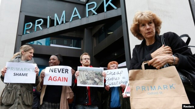 A shopper passes demonstrators outside clothing retailer Primark in central London, April 27, 2013.