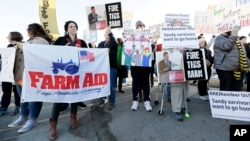 Protesters rally outside the Iowa Agriculture Summit in Des Moines, Iowa, where nine Republican presidential hopefuls discussed a variety of issues, March 7, 2015.