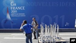 Men work near a G8 backdrop as preparations continue ahead of the G8 summit in Deauville, northern France, May 25, 2011
