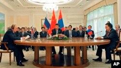 (L_R) Russian President Vladimir Putin, Chinese President Xi Jinping and Mongolian President Tsakhiagiin Elbegdorj meet on the sidelines of the Shanghai Cooperation Organization summit in Tashkent, Uzbekistan, June 23, 2016.