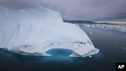 FILE - In this July 19, 2007 file photo, an iceberg is seen melting off the coast of Ammasalik, Greenland. A new assessment of climate change in the Arctic shows the ice in the region is melting faster than previously thought and sharply raises projectio