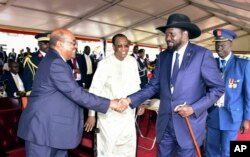 President Omar al-Bashir of Sudan, left, and President Salva Kiir of South Sudan shake hands during the inauguration ceremony of Uganda's long-time president Yoweri Museveni in the capital Kampala, May 12, 2016.