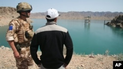 FILE - A British soldier stands with an Afghan interpreter with part of the Kajaki power dam in the background in Kajaki, Helmand province, south of Kabul, Afghanistan, April 16, 2008.