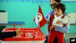 Une femme vote avec son enfant lors du premier tour de l'élection présidentielle tunisienne dans un bureau de vote à Marsa, près de Tunis, le 23 novembre 2014.