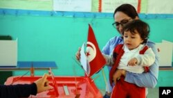A woman casts her vote with her child during the first round of the Tunisian presidential election Nov. 23, 2014.