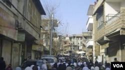Demonstran anti-pemerintah di pinggiran Damaskus menghadiri pemakaman rekan mereka yang tewas oleh pasukan keamanan Suriah (21/12).