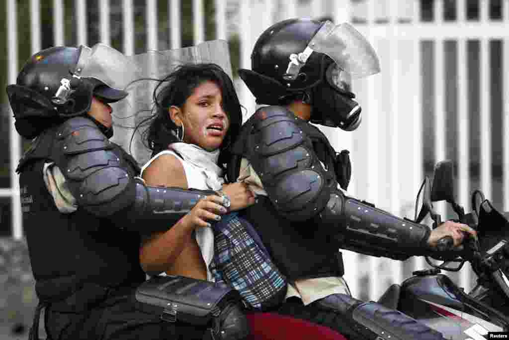 National police detains an anti-government protester during a protest against President Nicolas Maduro's government in Caracas, Venezuela, Mar. 13, 2014.