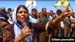 Dayikeke Kurd di mersîma binaxkirina kurê xwe de deng dike. Kobanê, Tîrmeh, 2014