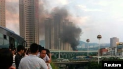 Warga setempat mengamati kepulan asap hitam dari bus yang terbakar di Xiamen, propinsi Fujian (7/6). Sedikitnya 42 orang tewas dan 33 terluka dalam insiden kebakaran tersebut.