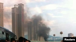 중국인들이 지난 해 6월 중국 동남부 푸젠성 샤먼에서 42명이 숨진 버스화재 현장을 바라보고 있다.