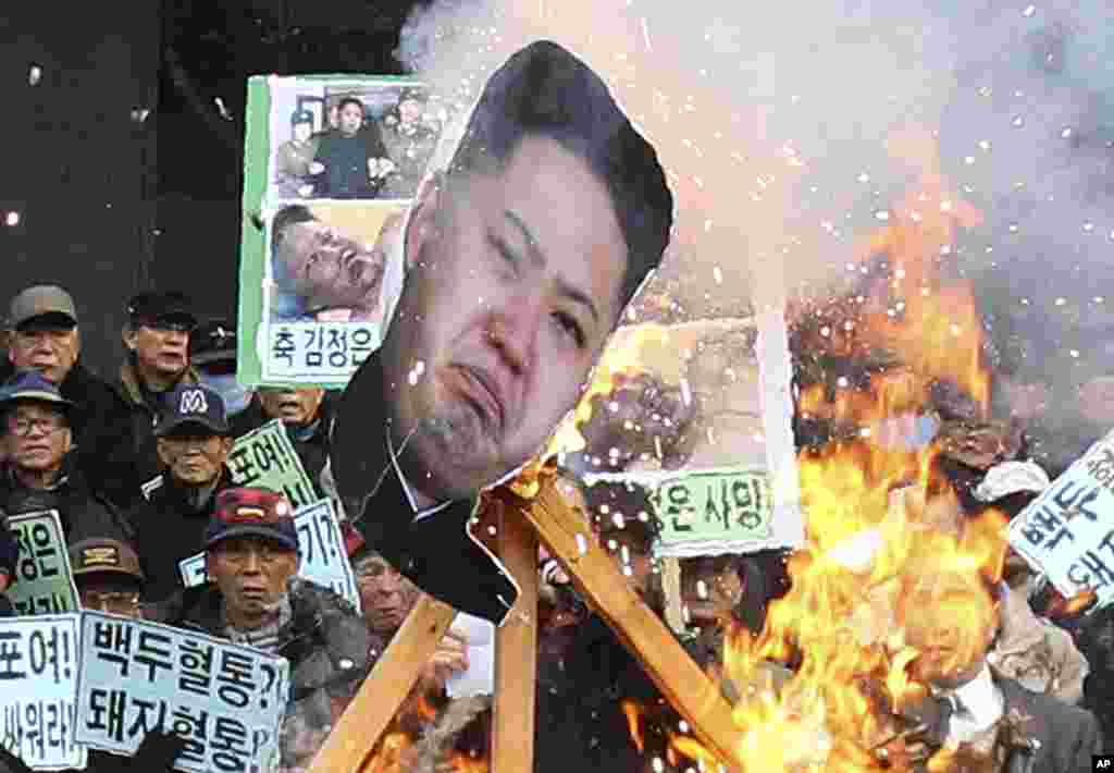 A portrait of North Korean leader Kim Jong Un is burned by protesters during an anti-North Korea rally marking the second anniversary of Kim Jong Il's death, Seoul, Dec. 17, 2013.