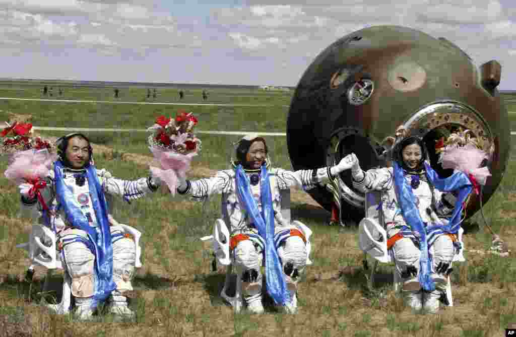 Chinese astronauts, from left, Zhang Xiaoguang, Nie Haisheng and Wang Yaping celebrate after getting out of the re-entry capsule of Shenzhou 10 spacecraft following its successful landing at the main landing site in Siziwang Banner, north China's Inner Mongolia Autonomous Region.