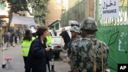 A woman enters a polling station guarded by soldiers and police during the first round of Egypt's run-off parliamentary elections in Cairo, December 5, 2011.