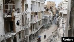 Des habitants d'Alep passant devant les bâtiments endommagés du secteur tenu par les rebelles syriens, le 5 mai 2016.