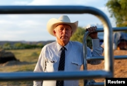 FILE - Rancher Cliven Bundy stands near a cattle gate on his 160 acre ranch in Bunkerville, Nevada, May 3, 2014. A federal judge declared a mistrial Wednesday, saying prosecutors had withheld evidence.