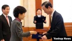 박근혜 한국 대통령이 25일 청와대에서 김장수 청와대 국가안보실장에게 임명장을 주고 있다.